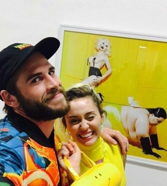 Here they are being cute AF in matching outfits at an art show in November.