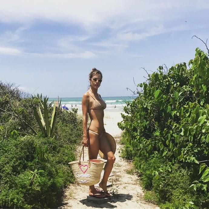 Alessandra Ambrosio schools us on beach bae fashion in her peach crochet bikini and matching tote.