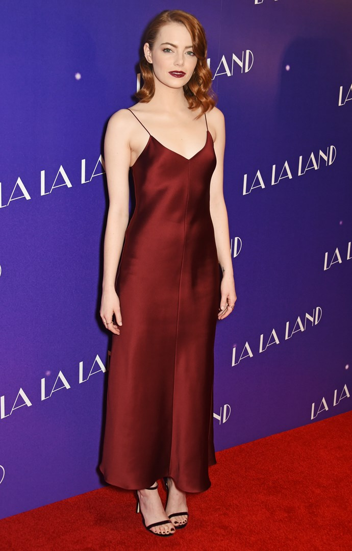 Emma Stone smouldered at the *La La Land* press tour in this deep burgundy slip dress and skipped the whole accessorising sitch 'cause this dress is fire enough as it is.