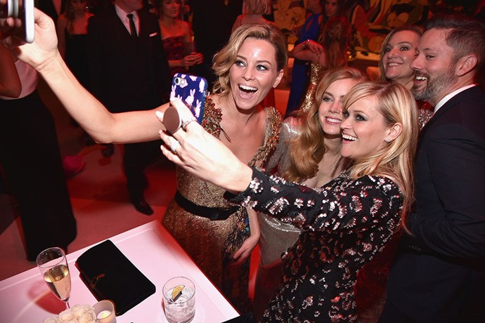 Selfie time for Elizabeth Banks, Amy Adams and Reese Witherspoon at the *Vanity Fair* Oscars party.