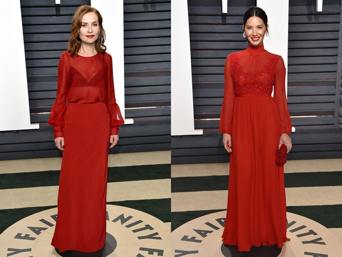 **Isabelle Huppert** and **Olivia Munn** in long sleeved, high necked red gowns with sheer tops.