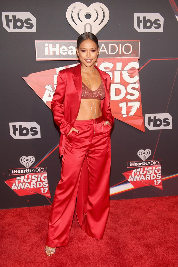 Karrueche Tran makes the pant suit hella sexy by opting for a scarlet red hue and replacing the top with a lil lace bralette.