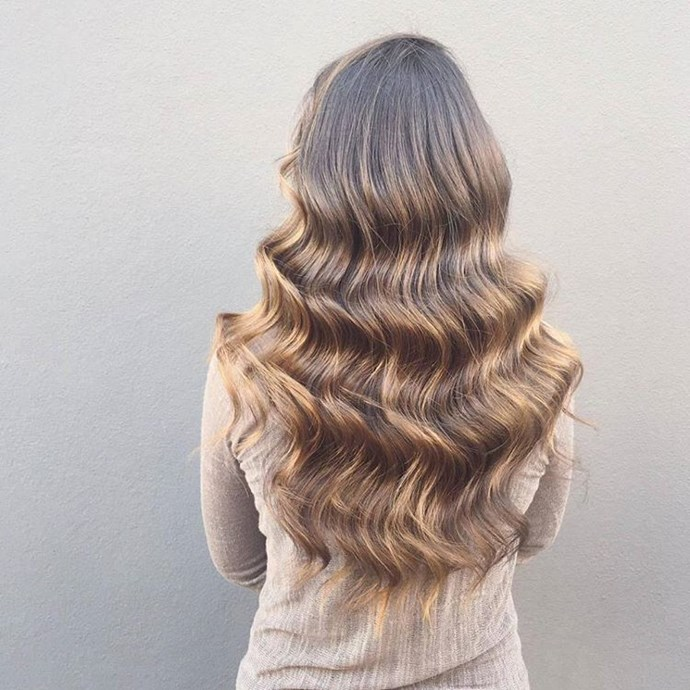 The trick to getting waves like these: Part your hair down the centre. Starting on the left side, wrap each 2.5 centimetre section around the barrel of a 2.5 centimetre iron until you reach the back of your head. Then repeat from the right side, until all your hair is curled. Then use a boar bristle brush to blend the curls together, making them look uniform.