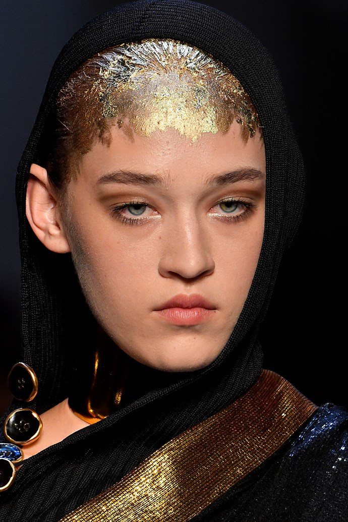 Makeup artist Stephane Marais and hair stylist Odile Gilbert were inspired by the heat of India, creating gilded the looks for the Jean Paul Gaultier show. Gold pigment was applied to the collar bones and shoulders, v-shaped part lines, the tips of the hair and around the eyes.