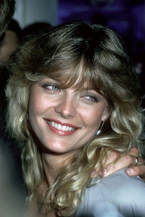 **1982: Feathered bangs** <br><br> If Michelle Pfeiffer's layered, fanned-out bangs don't give you serious *Grease 2* vibes, nothing will.
