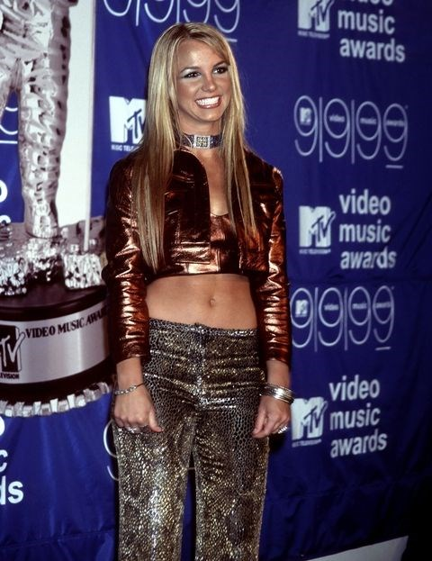 **BRITNEY SPEARS: 1999** <br><br> Britney is another superstar who has a very coloured VMA history. Do we even have to remind you of the Madonna snog, and performing *Slave 4 U* with an actual living python draped around her neck? <br><br> But at her first VMAs, Britney represented the true nineties pop princess she is. Wearing metallic errythang (including eyeshadow), she even made sure to add in a choker for good measure.