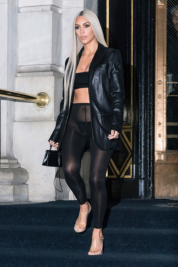 Kim Kardashian steps out at New York Fashion Week wearing a bikini with stockings and a jacket and, we're gonna be honest, we don't understand what the hell is going on here but girl looks like fire.