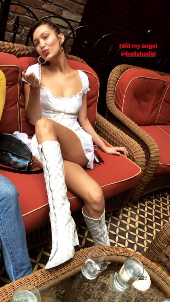 Bella Hadid wore a Little House on The Prairie dress with matching white knee-high boots for a lunch during the day.
