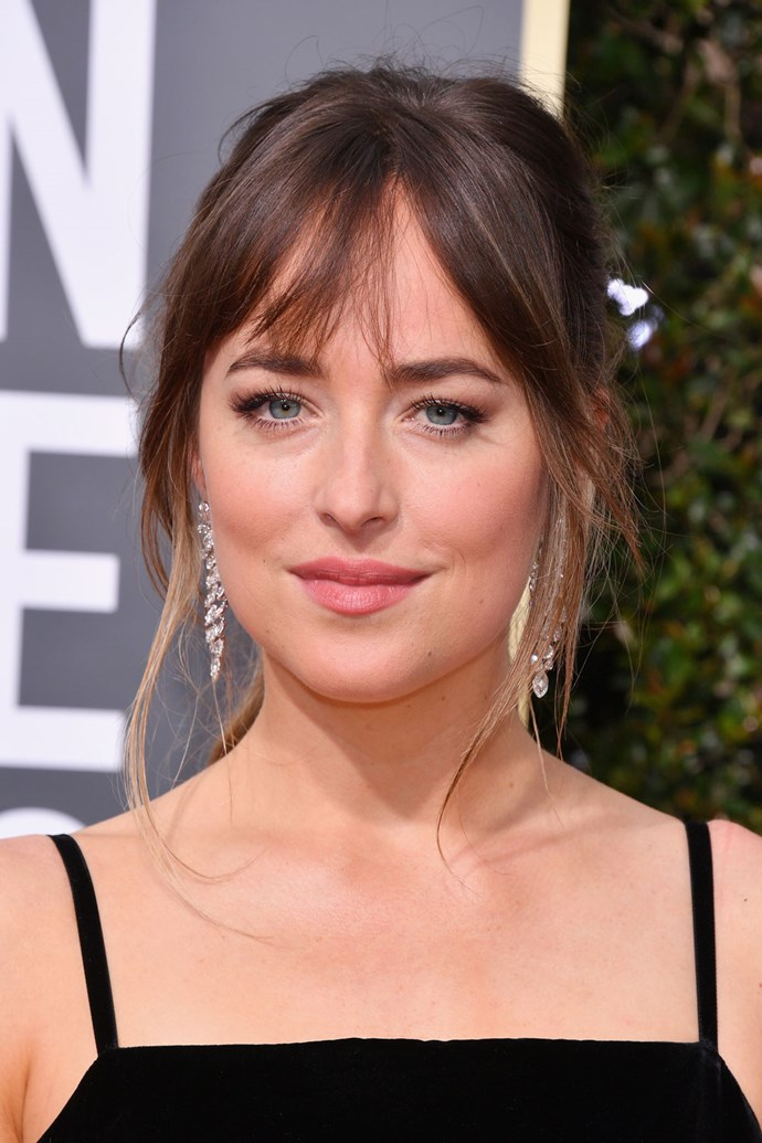 **Dakota Johnson** <br><br> This beauty look is classic Dakota! Here she reps her fave whispy bang/wavy ponytail comdo and completed her look with a rose-tinted lip.