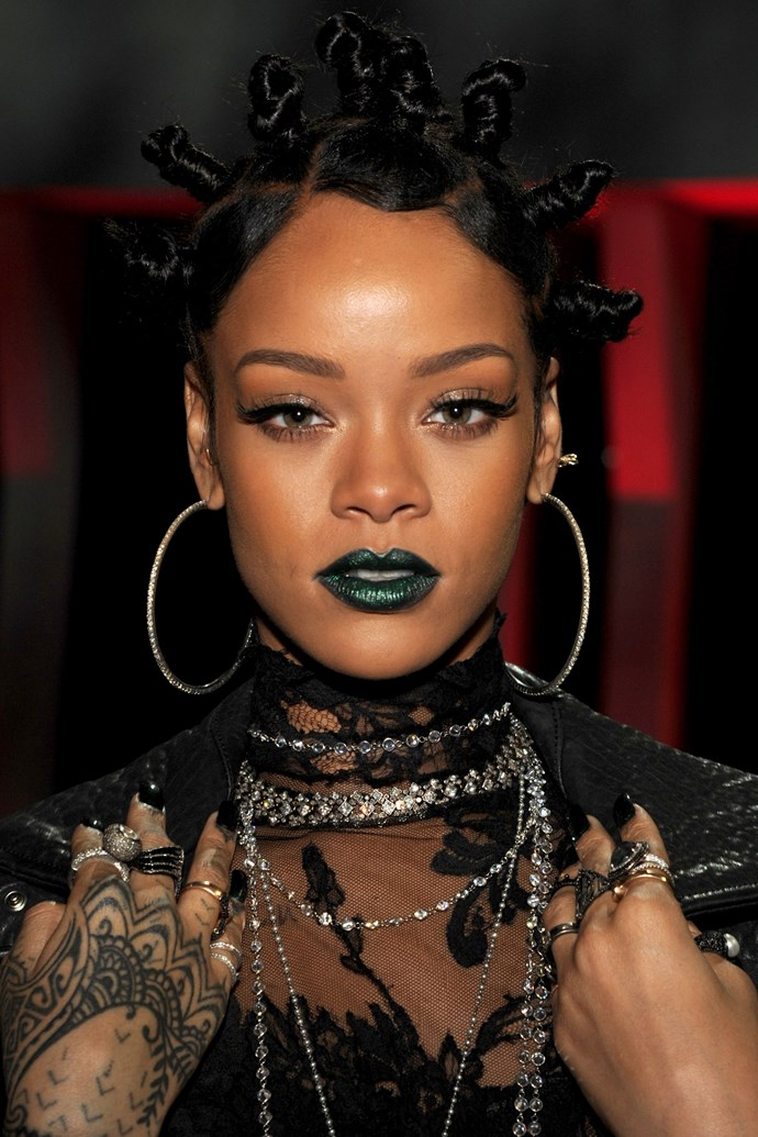 Rihanna channels a '90s Gwen Stefani, pairing her twisted buns with a metallic, emerald lip.