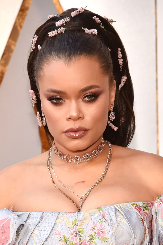 **Andra Day** <br><br> The singer song writer took this year's Oscars hair game to another level! Her voluminous pony was adorned with dozens of stems of pink lavender. Not to mention that stunning smoky winged eye and glossy lip to complement her floral tones.