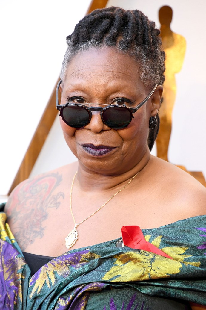 **Whoopi Goldberg** <br><br> The *View* host and actress turned it up on this year's red carpet, scooping her locs into an updo and sporting a ultraviolet lip to match her outfit.