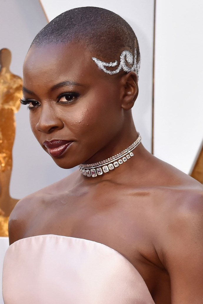 **Danai Gurira** <br><br> The *Black Panther* actress took Oscars hair game to another level, repping a gorge bright white pattern painted in her hair, a subtly smoky eye and glossy, mahogany lips.