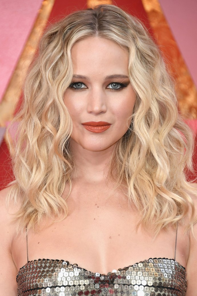 **Jennifer Lawrence** <br><br> The *Red Sparrow* actress channel 70s glam on this year's red carpet, channeling J-Law circa *American Hustle* with her mid-parted tumbling curls, strong smoky cat eye and terracotta lip.
