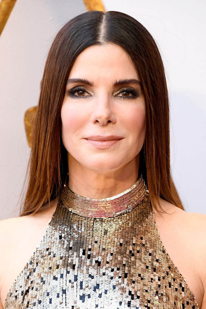 **Sandra Bullock** <br><br> The actress stunning in two-toned gold and black smoky eye, flushed cheeks, and super sleep middle-parted hair.
