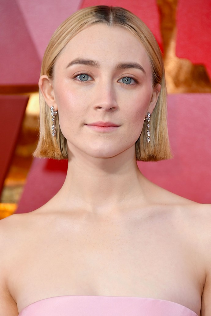 **Saoirse Ronan** <br><br> The *Lady Bird* actress served us serious feminine glam on this year's red carpet, pairing her mid-parted sleek bob with just a touch of blush pink on her lips and lids.
