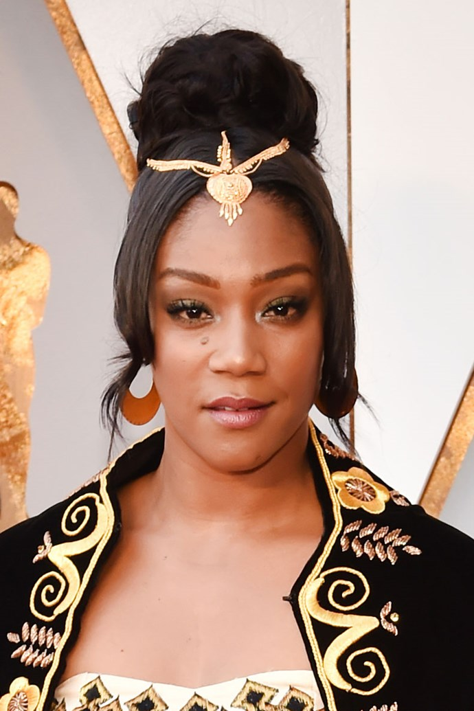 **Tiffany Haddish** <br><br> The *Girl's Trip* actress and comedian gave us serious regal with a braided bun topped with a gold headpiece, and a gold smoky cat eye.