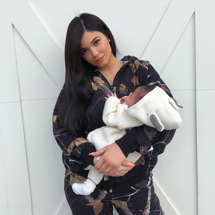 Kylie Jenner poses with baby Stormi outside her garage door marking the first official portrait of mum and bub.