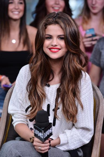Selena with long wavy strands and blonde highlights in 2013.