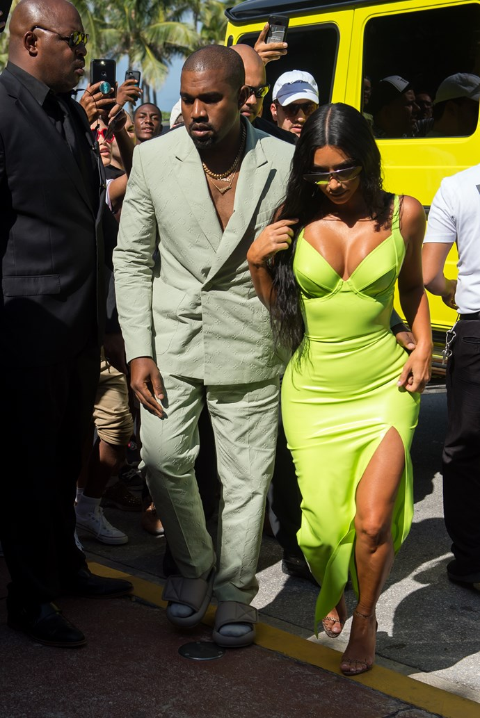 With husband Kanye, attending the wedding of rapper 2 Chainz. Matching neon car again, duh! *(Image via Splash News.)*