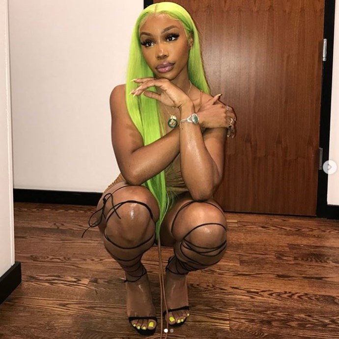 RNB queen SZA sporting a neon 'Kimmy' weave and matching nails.