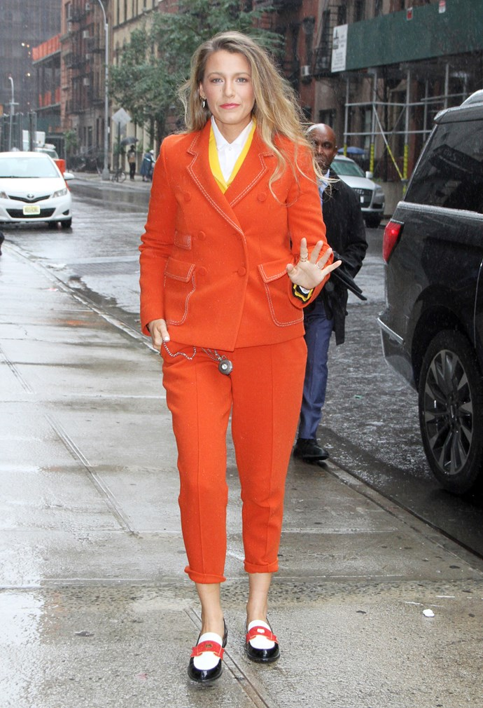 A bold orange look complete with pocket watch. This woman commits.