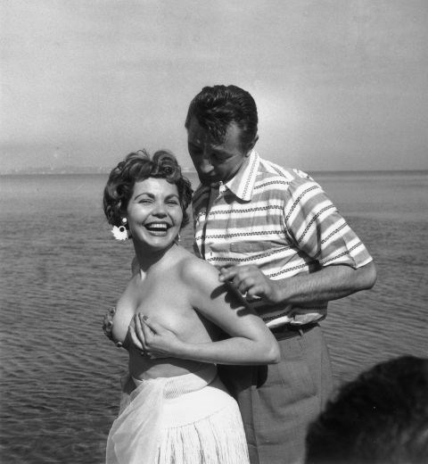 **SIMONE SILVA AND ROBERT MITCHUM, 1954**  When Simone Silva posed topless at Cannes, she inspired a melee where one photographer broke his arm and another broke his leg. She was later asked to leave the festival.