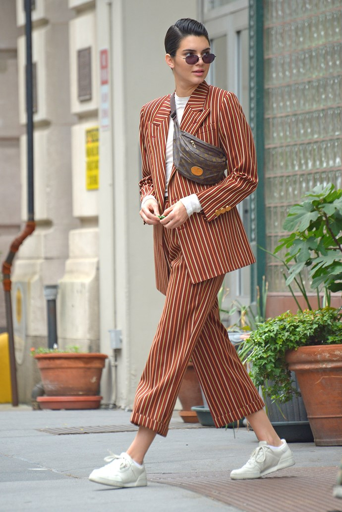 Kendall was spotted in New York wearing a sharp orange pin-stripe suit, which she paired with a slick hairstyle, a Louis Vuitton fanny pack and white sneakers.