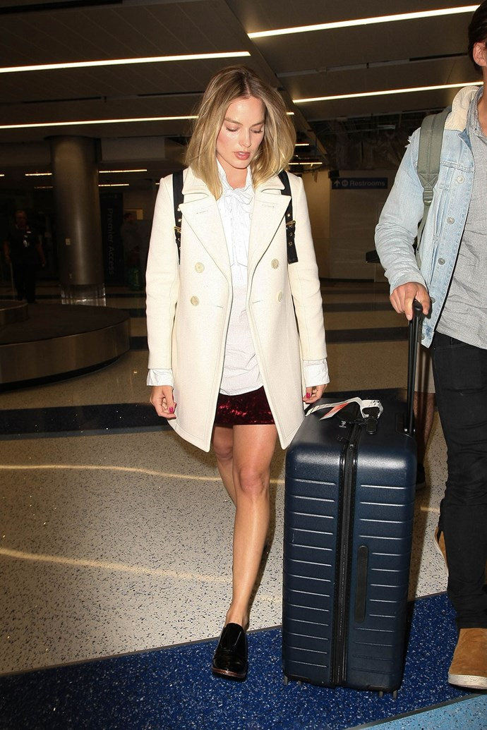Margot spotted at LAX in a cream coat and brogues.