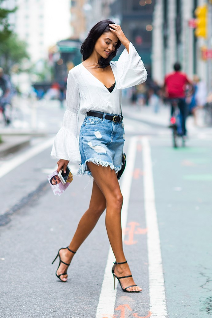 **Shanina Shaik:** A frayed denim skirt + boho blouse + black heels + peek-a-boo lace bra = the ultimate off-duty look with just a hint of sexiness. Perfect for spring weekends when your plans take you from day to night.