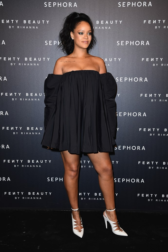 Rihanna showcased Fenty Beauty in Paris a Jardin des Tuileries, in a short, black, off-the-shoulder Calvin Klein mini dress with puffy sleeves and white heels.
