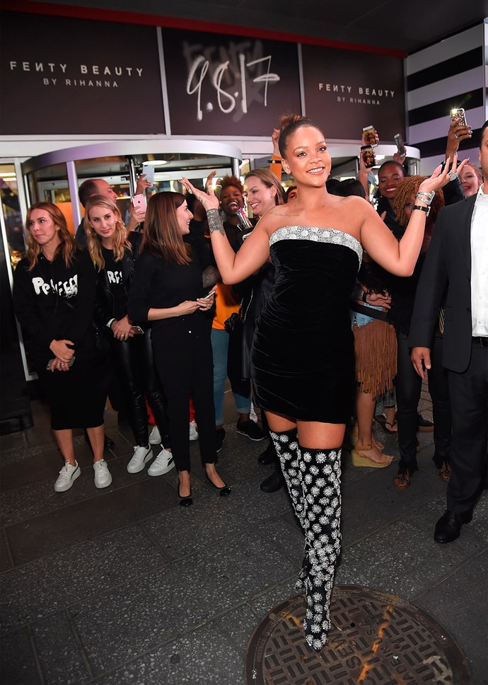 Rihanna launches Fenty Beauty at the Sephora in Times Square, New York City—wearing a short, strapless dress, with a beaded trim and pairing  it with bedazzled thigh-high boots.