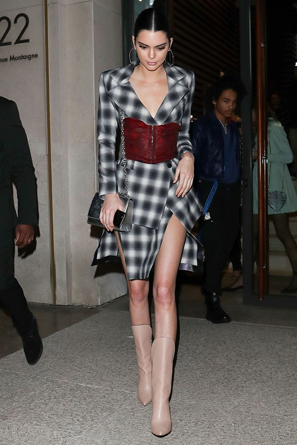 Kendall Jenner left a party in Paris wearing a Louis Vuitton plaid skirt suit, adding a contrasting corset for a modern edge.