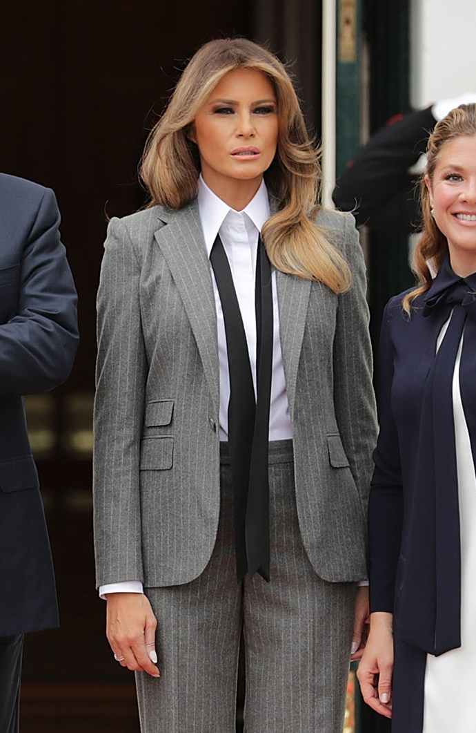 Melania Trump breaks the FLOTUS outfit mould with her grey pinstriped suit paired with a loose tie.