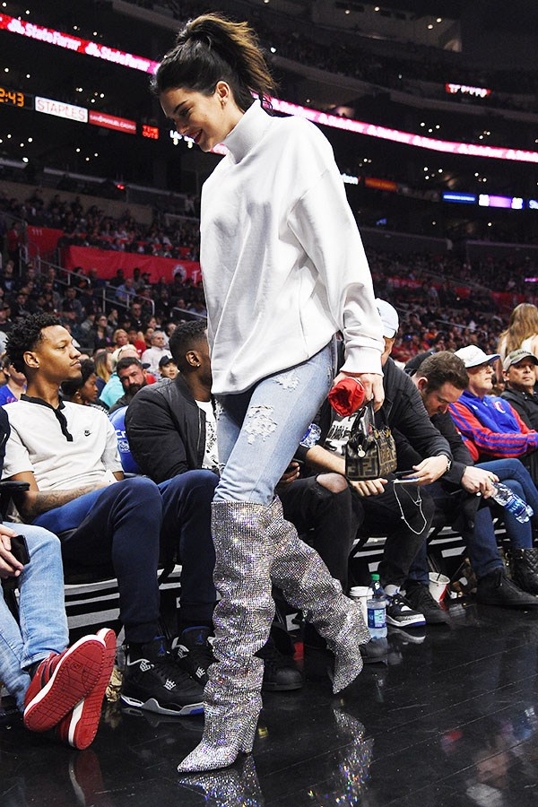 In Saint Laurent boots at the LA Clippers vs. Memphis Grizzlies game. November 4th, 2017.