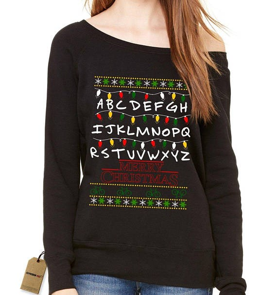 "Stranger Things Christmas Lights Sweatshirt, $23.27 from [Etsy](https://www.etsy.com/listing/557806455/strange-merry-christmas-ugly-holiday|target=""_blank"")."