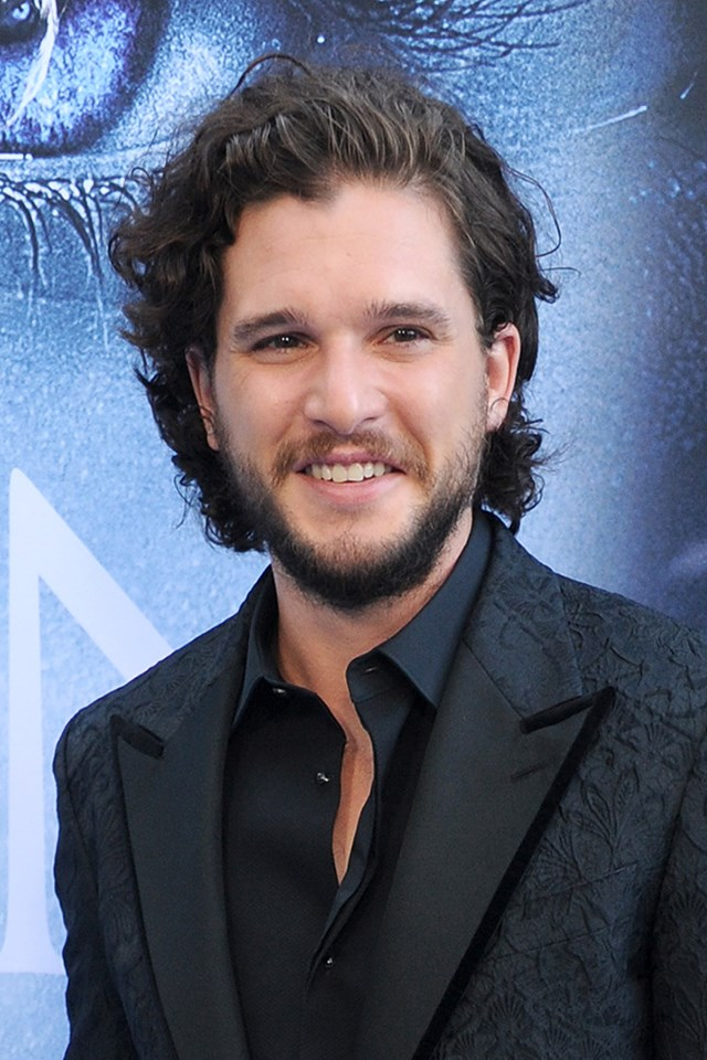 """**Kit Harington** <br><br> There are two things we think of when we think of Kit Harington: Jon Snow and his hair. The actor has joked that once *Game of Thrones* is over, he plans to """"shave off"""" his dark mop of curls, but we hope he's joking. Also, he wears the best man bun in Westeros."""