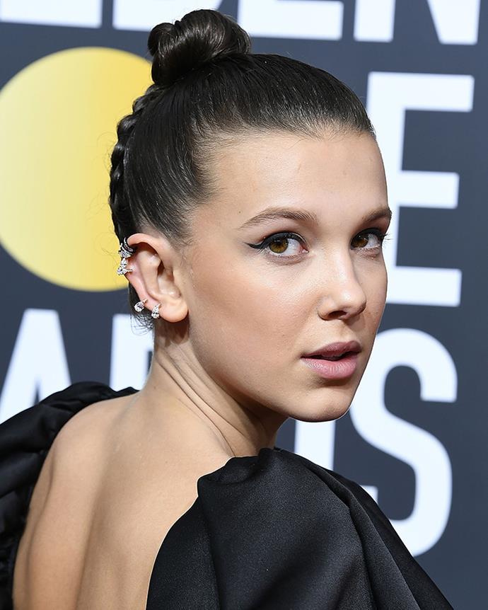 **Reverse Triple-Braided Top Knot** <br><br> For the 2018 Golden Globes, Blake Erik seamlessly plaited Brown's hair all the way up into a sleek top knot in three Dutch braids. Fans also noticed that [Brown's hair contained a secret message](https://www.elle.com.au/beauty/millie-bobby-brown-golden-globes-hairstyle-eleven-15523)—whether intentional or not, the lines formed by the braids read '11', like her character on *Stranger Things*.