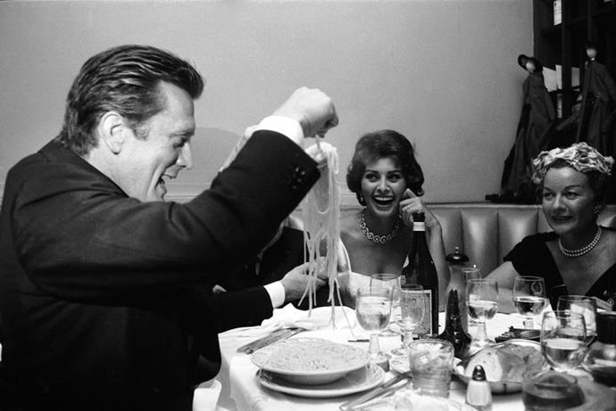 Kirk Douglas scoops up some spaghetti and Sophia Loren is obviously delighted. New York, New York, June 1958.