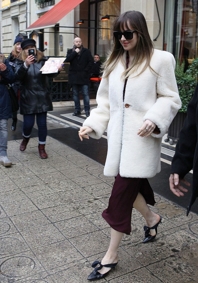 Dakota Johnson dressed like a true French girl while in Paris for the *Fifty Shades Freed* premiere, wearing a crimson midi dress, black bow kitten heels and an ivory teddy coat.  Image: Splash