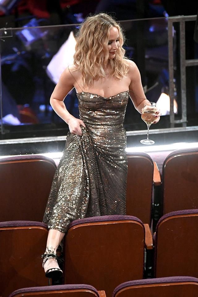 Jennifer Lawrence stepping over seats at the 2018 Oscars.