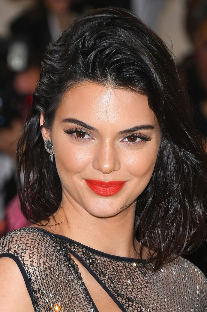 Kendall Jenner attends the 2017 Met Gala sporting fluttery lashes and a bright, coral red lip.
