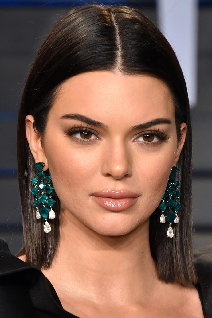 Kendall Jenner attends the 2018 Vanity Fair Oscar Party with pouty nude lips and a subtle smokey eye.