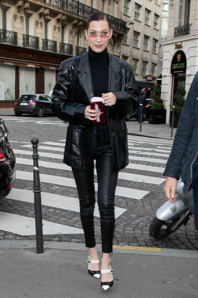 **Bella Hadid** in a matrix-inspired long jacket.