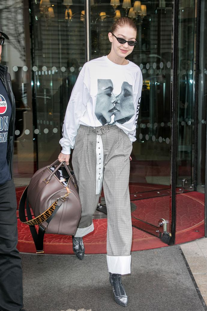 Gigi Hadid stepped out in Paris wearing a Chaos SixtyNine graphic tee—which features a kiss shared between Cara Delevingne and Adwoa Aboah—paired with cuffed houndstooth trousers, sock boots and a Fendi duffle bag.