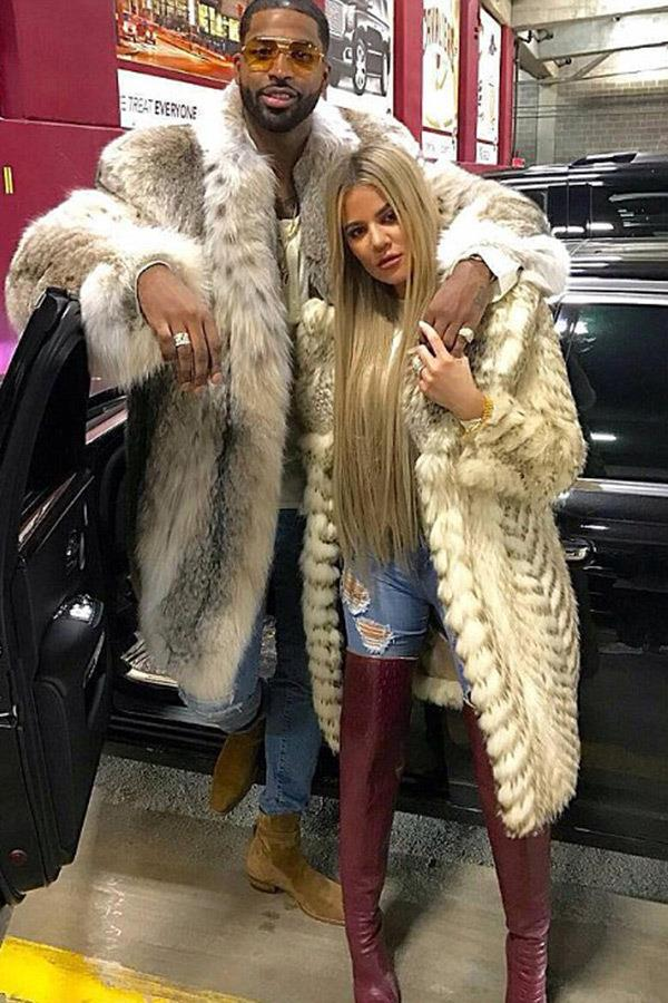 Khloé Kardashian and Tristan Thompson posing in fur next to their car. (Sourced from Instagram.)