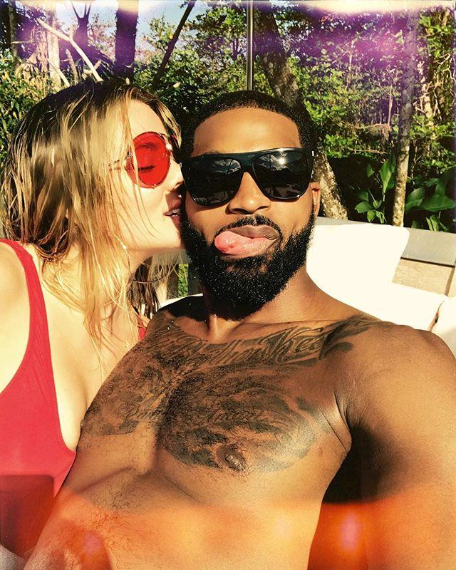 Khloé Kardashian and Tristan Thompson getting cosy poolside. (Sourced from Instagram.)