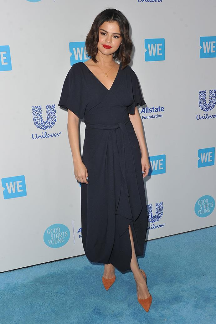 Selena Gomez stepped out at WE Day California wearing a navy wrap dress and burnt orange heels (with a quirky heel), both by Jacquemus.