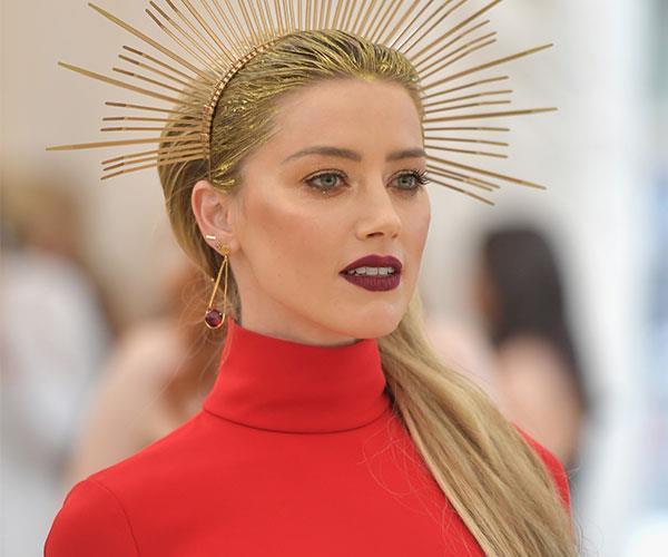 **Amber Heard** <br> Heard's head piece is hard to miss. After you've taken a moment to process the gold points, we'd like to draw your attention to her dark mauve lipstick, bronzed cheeks and metallic eyes.