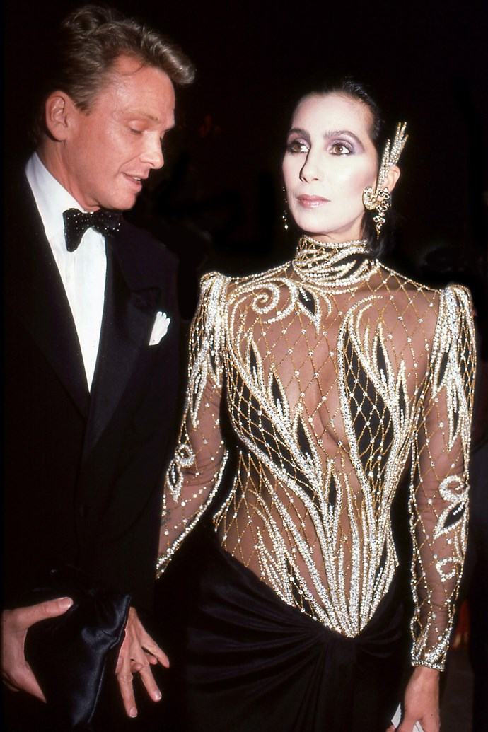 **1985: CHER in Bob Mackie** <br><br> Before the naked dress was a staple item of Beyoncé and Jennifer Lopez (and even Marc Jacobs), Cher pioneered the look in an era where showing your body was considered significantly more risqué.  <br><br> Her long-running collaboration with designer Bob Mackie produced a dizzying array of naked dresses that caused somewhat of a public meltdown—pictured here in a custom gown at the 1985 Met. Not all fashion heroes wear capes.